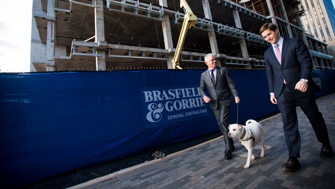 John McKibbon, left, chairman of McKibbon Hotel Group, walks his dog Charlie, an American Bulldog/Shar-Pei mix, along a plaza walkway where his company is set to open an Aloft hotel later this year. With him is Robert Hughes, chief operating officer of Hughes Development Corp.