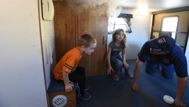 Fire inspector Eddie White leads Gassville brother and sister Nicholas and Alizabeth Armstrong through the Mountain Home Fire Department's smoke house during the Third Annual North Central Arkansas Emergency Preparedness Fair on Saturday. The event, held at the Baxter County Fairgrounds, gave citizens the opportunity to connect with emergency responders and receive information about preparing for disasters. The event was well attended, according to organizers.