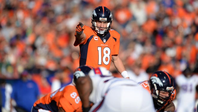 Denver Broncos quarterback Peyton Manning (18) points from the line of scrimmage in the first quarter against the Buffalo Bills at Sports Authority Field at Mile High.
