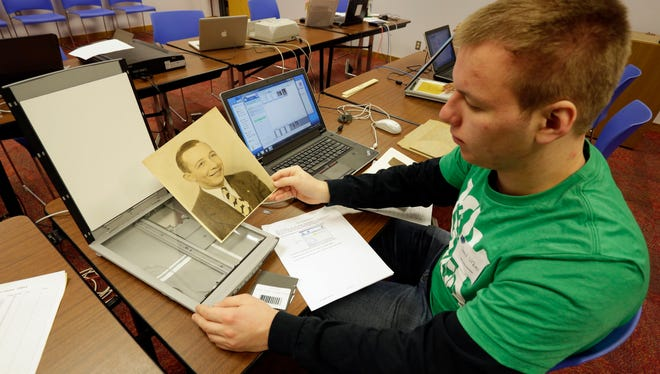 Volunteer Jared Urban of Oostburg,17, prepares to scan a vintage portrait Saturday March 5, 2016 at City of Sheboygan History Scan Day held at Mead Public Library.