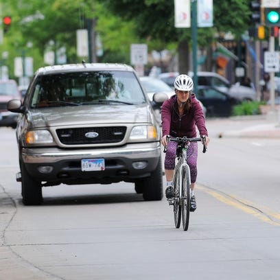 Kerrie Vilhauer, of Sioux Falls, rides a bicycle North on Phillips Avenue through downtown Sioux Falls on Tuesday, May 26, 2015.