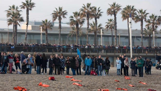 People stand past life jackets spread on the beach during a demonstration to demand to welcome refugees in Barcelona on Feb. 18, 2017.