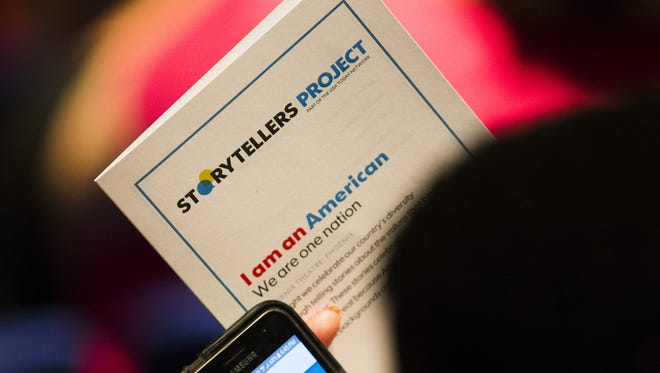 "A guest holds a program during the Storytellers Project ""I am an American"" storytelling event at Phoenix Theatre June 14, 2017."