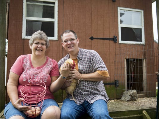 """Lore and Jim Schwenk pose with one of their chickens in the backyard of their home in Schaefferstown. Jim says the fowl take more to Lore, who he calls the """"chicken whisperer."""""""