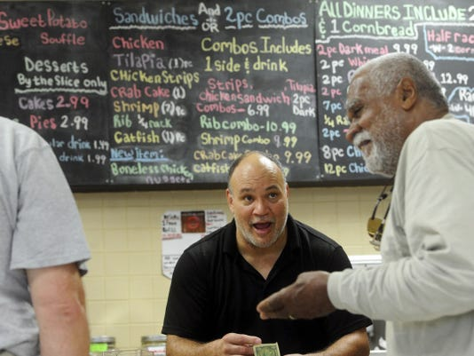 """Brad Carr, center, jokes around with customers in his Phoenix soul food restaurant, Ezekiel's. Serving food has become a ministry of sorts for him and his wife, Rita. """"We could just about cook anywhere in York and have good clientele,"""" he said. """"Coming out here, it's so spread out, so we just have to get our niche. It's catching on ... """""""