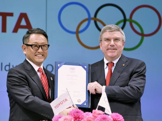 IOC President Bach and Toyota Motor Co. President Toyoda hold their agreement document to become part of the IOC's top sponsorship programme, during a news conference in Tokyo