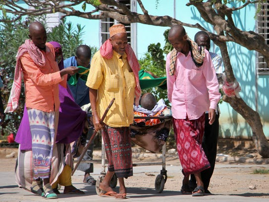 Somalis help a civilian wounded in Saturday's blast,