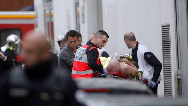 """An injured person is treated outside the office of the French satirical newspaper """"Charlie Hebdo"""" in Paris on Jan. 7, 2015."""