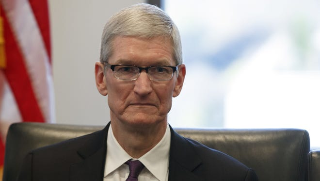 Apple CEO Tim Cook listens as President-elect Donald Trump speaks during a meeting with technology industry leaders at Trump Tower.