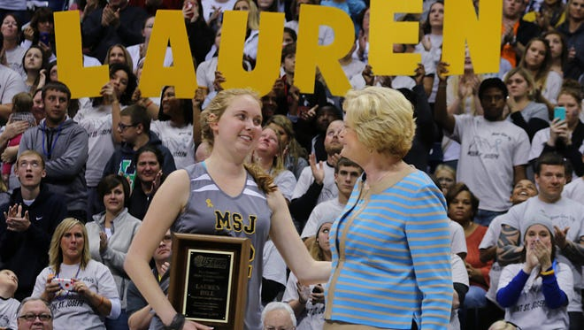 FILE - In this Nov. 2, 2014, file photo, Mount St. Joseph's Lauren Hill, left, smiles at Pat Summitt after receiving the Pat Summitt Award during halftime of her first NCAA college basketball game against Hiram University at Xavier University in Cincinnati. Hill is using her limited energy and her final days to try to inspire people and raise money for research into the cancer that is taking her life. (AP Photo/Tom Uhlman, File)