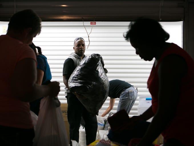 Volunteer Steve Kabiru (center) helps with the organization