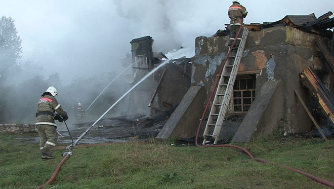 Firefighters work at a site of a fire at a psychiatric hospital in Luka village in the Novgorod region, Russia, Sept. 13, 2013.