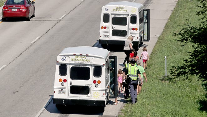 Children are escorted to a Bright Beginnings Childcare and Learning Center bus after the bus they had been riding in was involved in a traffic crash Tuesday on northbound Interstate 43 in Green Bay.