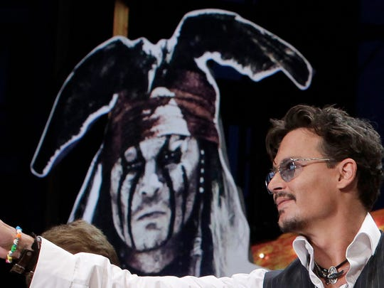 Actor Johnny Depp waves for fans during the Japan premiere