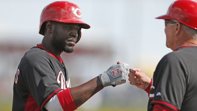 Brandon Phillips bumps fists with third base coach Steve Smith.