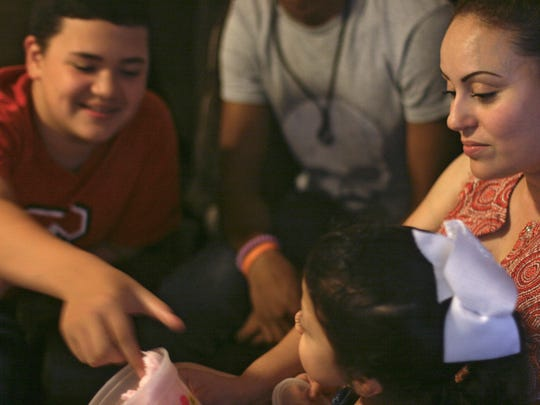 Andrew Buscamante-Madrid, 12, plays with his half-sister Allison Hernandez-Madrid, 5, while their mother, Luz Madrid watches.