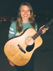 Jenna Terek of Wausau shows off the guitar autographed