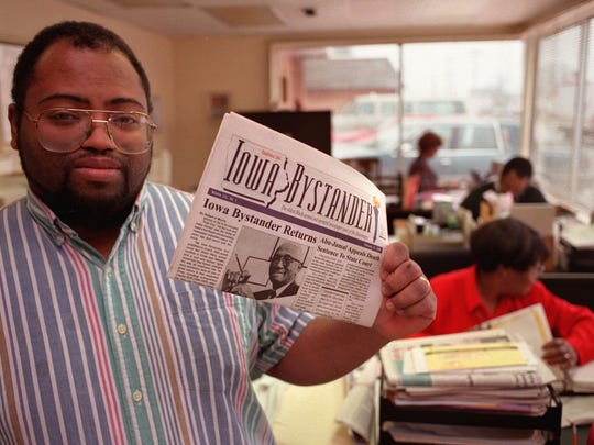 Jonathan Narcisse, publisher of the Bystander, holds up an issue of the paper as his small staff works in the background on February 26, 1996.