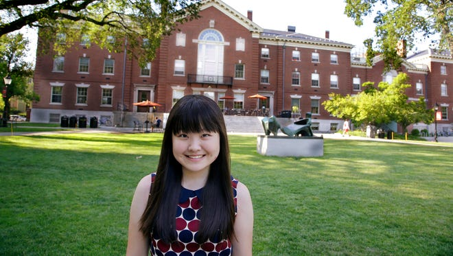 In this Thursday, July 10, 2014 photo, Lisa Li, a high school student at the U.S. prep school Lawrence Academy in Groton, Mass., poses for a photo outside the Stephen Robert Campus Center on the Brown University Campus in Providence, RI.