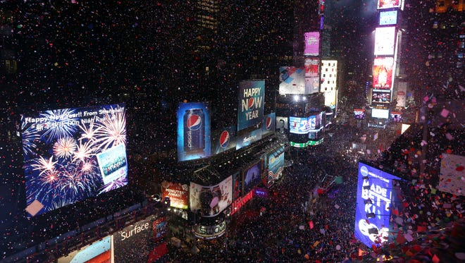 In this Jan. 1, 2013, file photo, donfetti flies over New York's Times Square after the clock strikes midnight during the New Year's Eve celebration as seen from the Marriott Marquis hotel in New York. As Americans prepare to ring in 2014, they look to the new year with an optimistic eye, according to a new AP-Times Square New Year's Eve poll, while their ratings of the year gone by are less than glowing.
