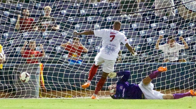 Arizona United forward Jonathan Okafor slides the ball past Pittsburgh Riverhounds goalkeeper Mike Lisch for the game's first goal in Arizona United's 3-1 win over the Pittsburgh Riverhounds Aug. 16 at the Peoria Sports Complex.