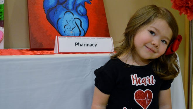 Miya Hawley stands near her mother's art piece at the Show us Your Heart art show at Kaweah Delta Medical Center. Miya was born with a rare heart defect where a portion of the aorta blood vessel is narrowed.