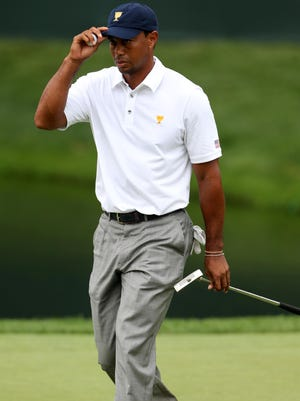 Tiger Woods tips his hat to the gallery on the 16th green during the fourth round of the Presidents Cup in 2013. The focus on Woods in 2014 will be his performance in the major tournaments.