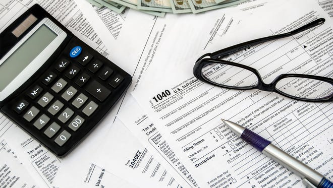 Tax form with pen, glasses, dollars and calculator