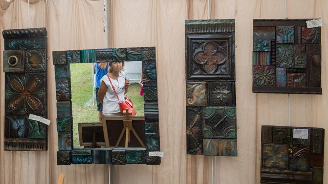 Donna Deatherage of East Peoria is reflected in a piece of art while perusing the work offered by April Sepich, a former Peoria artist now residing and working in Wisconsin, at a past Washington Fine Arts Festival in Washington Park.