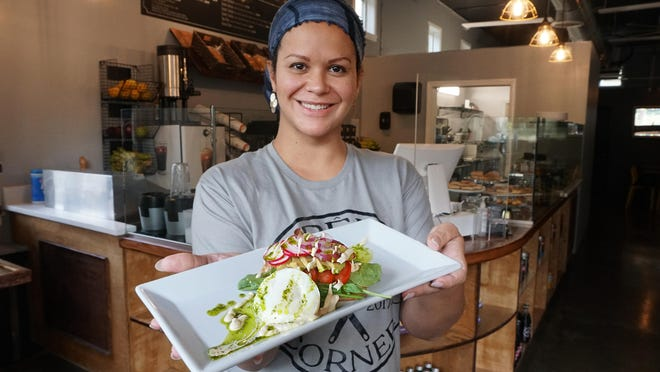 Natacha Legein, owner of Crepe Corner, holds a Brussels breakfast special with poached egg, bacon, cheese, tomato, radish, pesto, red onion, on a bed of hash.