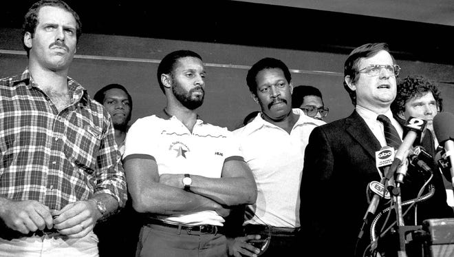 In this Nov. 16, 1982 file photo, with players behind him, the NFL's chief negotiator Ed Garvey addresses the media. From left are Dave Stalls, Tampa Bay; Burgess Owens, Los Angeles Raiders; James Lofton, Green Bay Packers; Gene Upshaw, L.A. Raiders, Garvey and Stan White, Detroit Lions.