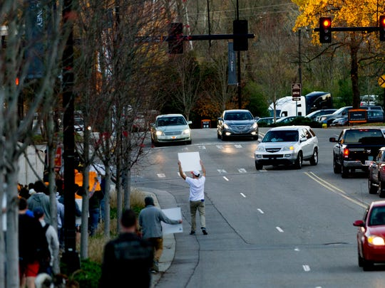 A marcher walks into the street with their sign during a protest against the possible hiring of Greg Schiano outside of Neyland Stadium in Knoxville, Tennessee on Sunday, November 26, 2017.