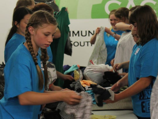 Annamarie Aue sorts donated clothing at the Community Action Coalition for South Central Wisconsin.