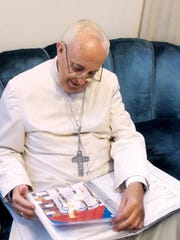 "Pope Francis looks over a binder of questions and illustrations from children around the world at the Vatican. He chose 30 of their questions to answer and include in a new book, ""Dear Pope Francis,"" out March 1 from Loyola Press."