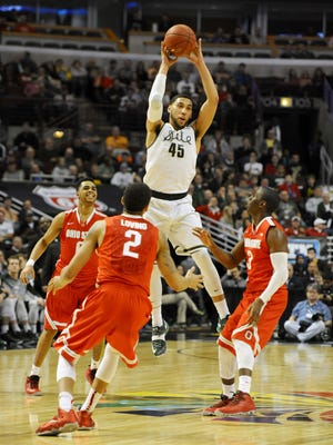 MSU's Denzel Valentine leaps to snag a loose ball  against Ohio State defenders during their Big Ten Tournament game Friday night in Chicago. Valentine finished with 23 points, eight rebounds and seven assists.