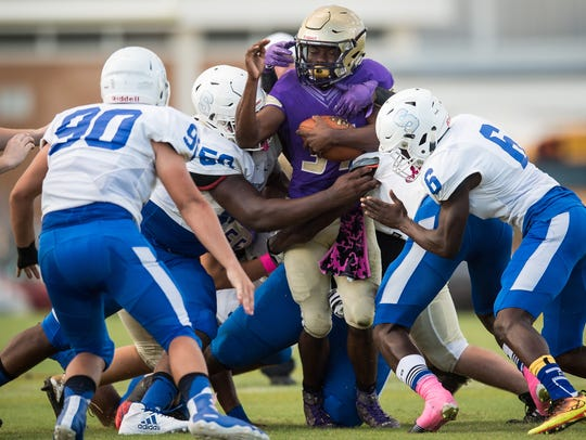 Okeechobee's Lamar Williams (center) is brought down