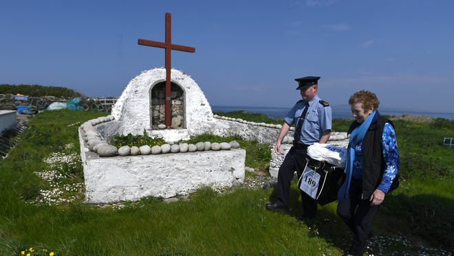 Garda Alan Gallagher and Presiding Officer Carmel McBride carry a polling box, used, a day early, by the few people that live off the coast of Donegal on the island of Inishbofin on May 24, 2018 in Donegal, Ireland.