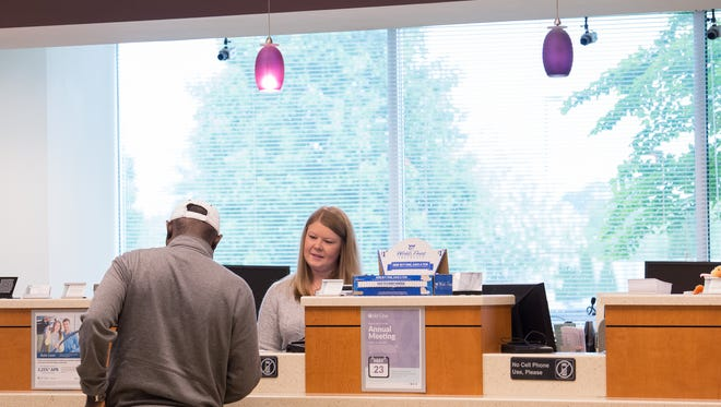Del-One Federal Credit Union teller Samantha Morgan waits on a member at its Dover branch.