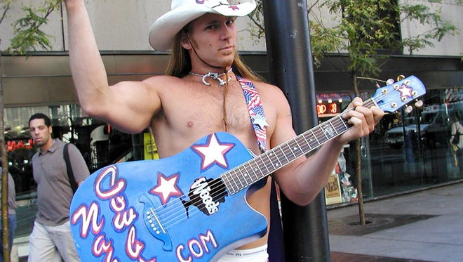 Robert John Burck, the Naked Cowboy, plays his guitar and poses for photos in New York's Times Square.