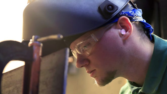 Brandon Hyde, 25, inspects his work after welding together two pieces of metal in a class at Northeast Wisconsin Technical College. After leaving the military, Hyde had problems with drug and alcohol abuse.