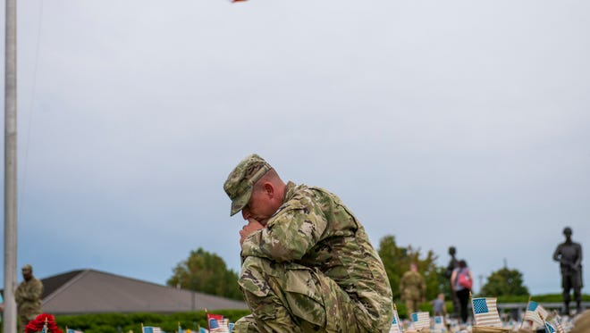 Robert Reynolds, son-in-law of U.S. Army Garrison Fort Campbell Command Sergeant Major Noel Foster, kneels by his boot during a ceremony for fallen soldiers on September 11, 2017. CSM Foster died September 1 in his home.