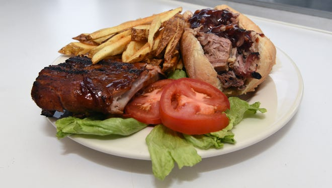 A platter of barbecue ribs, pulled pork sandwich and handcut fries are shown at Hickory Lane Barbeque & Grill. The food truck offers a variety of smoked meats, including ham, turkey and sausage.