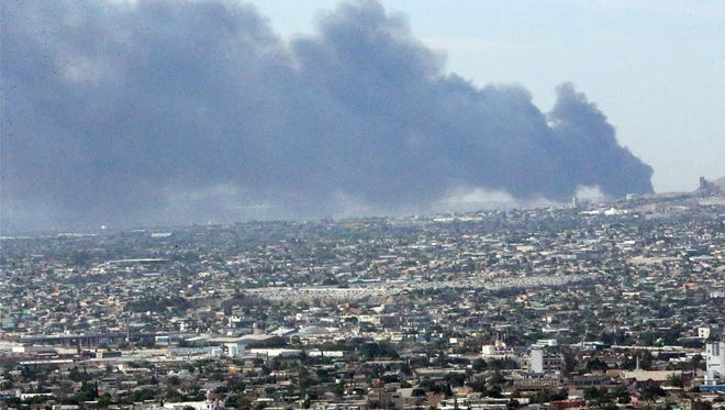 Heavy plumes of smoke are seen rising from the outskirts of Juarez Wednesday morning in this photo taken from El Paso's Scenic Drive. The smoke was caused by a fire at a recycling plant in Juarez. The fire was 90 percent contained by Wednesday night.