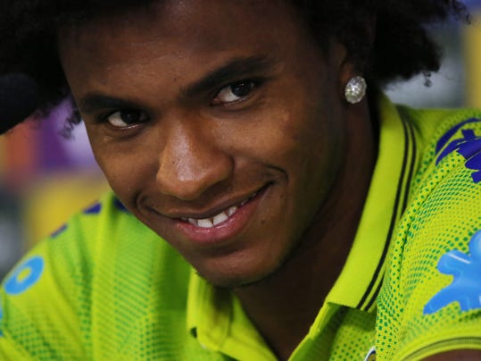 Brazil's Willian smiles as he listens to a question during a press conference at the Granja Comary training center in Teresopolis, Brazil, Sunday, July 6, 2014.  Brazil will face Germany on Tuesday in their World Cup semifinals' match, without superstar soccer player Neymar. (AP Photo/Leo Correa)