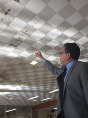 Grambling State University President Rick Gallot points to mold or mildew on the ceiling of A.C. Lewis Memorial Library, which he said the university will abandon before April.
