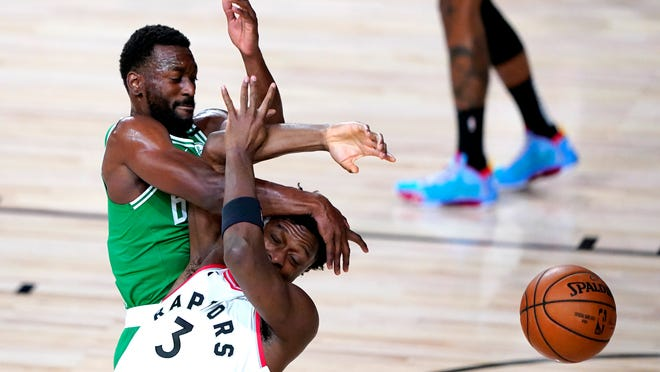 The Celtics' Kemba Walker, top, and the Raptors' OG Anunoby collide while competing for possession during the first half.