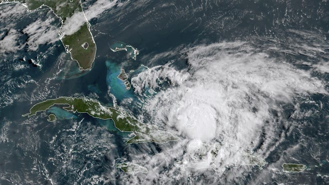 In this GOES-16 satellite image taken Friday, July 31, 2020, at 8:40 a.m. EDT., and provided by NOAA, Hurricane Isaias churns in the Caribbean. Hurricane Isaias kept on a path early Friday toward the U.S. East Coast as it approached the Bahamas, parts of which are still recovering from the devastation of last year's Hurricane Dorian.
