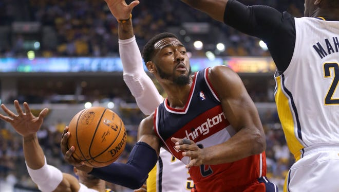 Washington Wizards guard John Wall passes the ball off from under the basket during the second half of action. Indiana Pacers play the Washington Wizards in game 2 of the Eastern Conference Semifinals, May 7, 2014, at Bankers Life Fieldhouse.