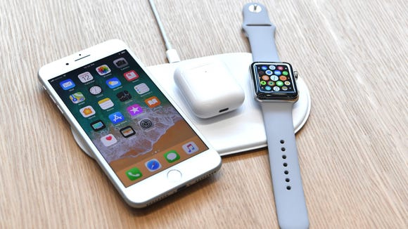 An AirPower mat is seen charging multiple devices.