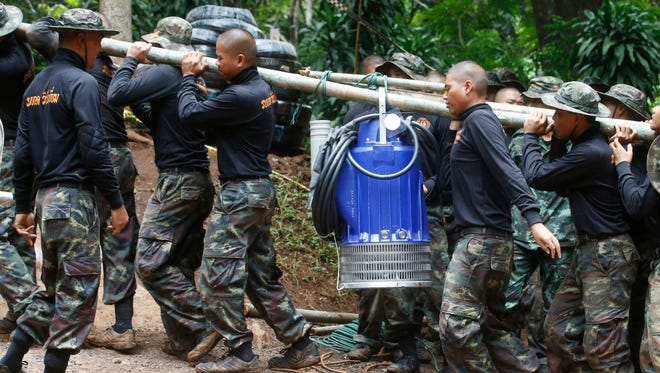 Soldiers carry a pump to help drain the rising flood water in a cave where 12 boys and their soccer coach have been trapped since June 23, in Mae Sai, Chiang Rai province, in northern Thailand Friday. Thai authorities are racing to pump out water from the flooded cave before more rains are forecast to hit the northern region.